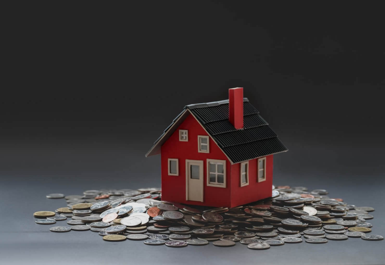 Avoid Costly Problems with an Apartment Pre-Purchase Building and Pest Inspection from Total Inspections. Image featuring miniature figurine of red house surrounded by small pennies and coins