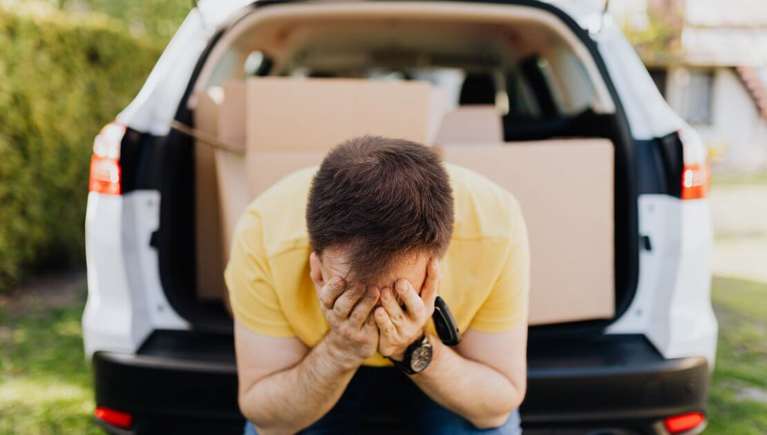 Avoid Costly Problems with an Apartment Pre-Purchase Building and Pest Inspection from Total Inspections. Image featuring man with palms over his face sitting on the boot of his car with packing boxes inside white van. Stressed man about to move in to a new home or apartment.