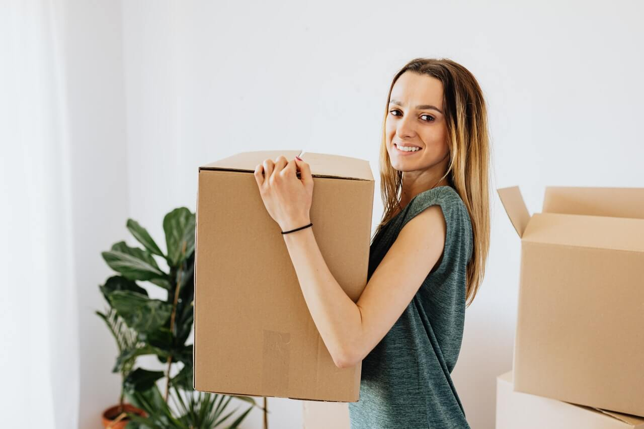 Avoid Costly Problems with an Apartment Pre-Purchase Building and Pest Inspection from Total Inspections. Image featuring young woman holding up cardboard box packed full about to move in to new apartment.