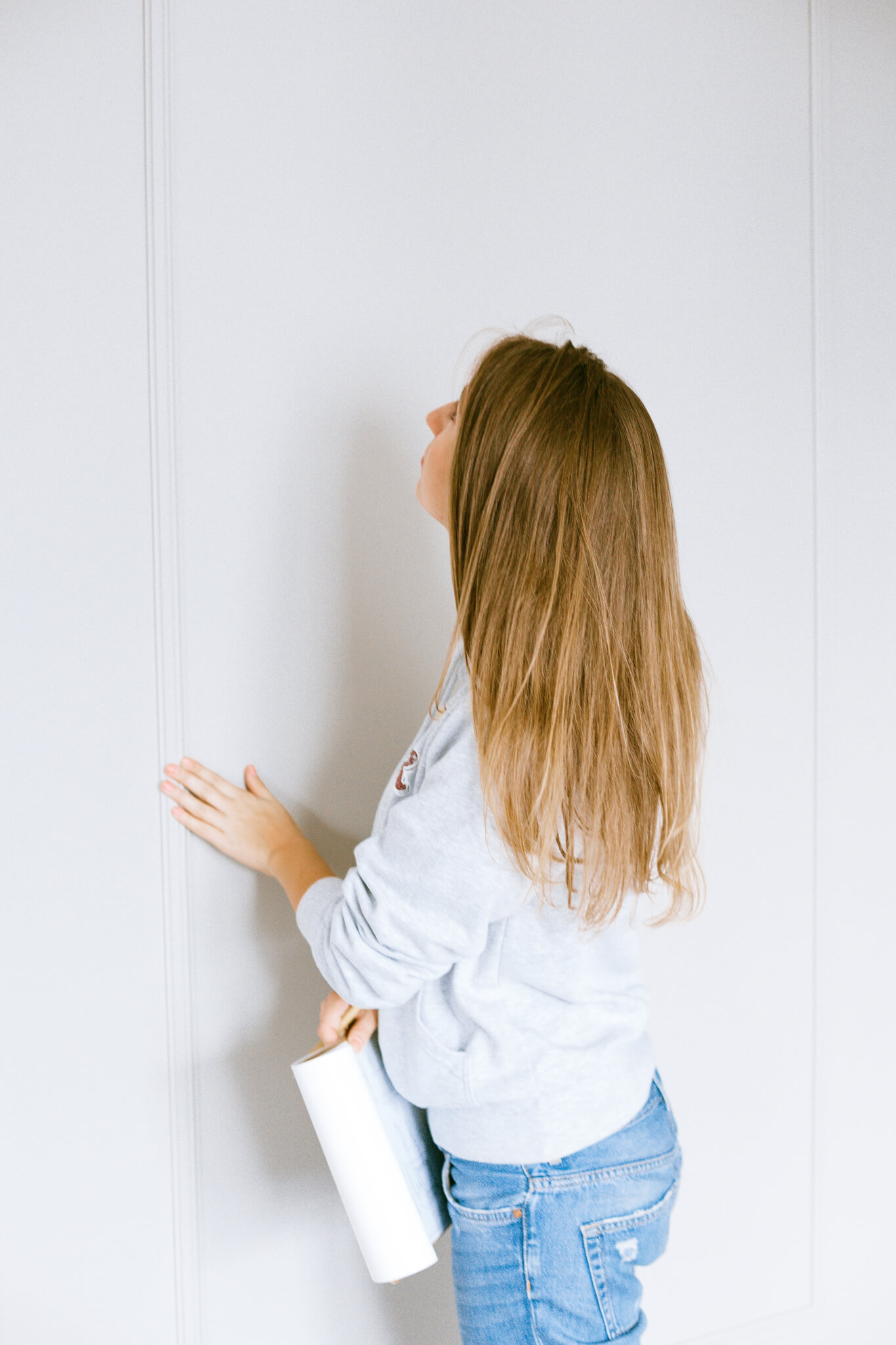 pre purchase and pre sale building and pest inspections for total inspections blog woman checking white wall in her home holding clipboard Asbestos Inspections and Testing in Australia | Why you need it